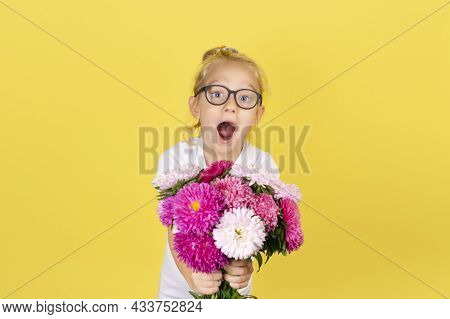 Child Girl Holding Bouquet Of Beautiful Pink And White Aster Flowers Isolated On Yellow Background.