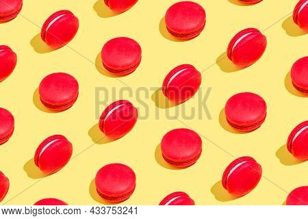 Creative Pattern Made Of Red Macaroons On Yellow Background. Dessert And Confectionary Concept.