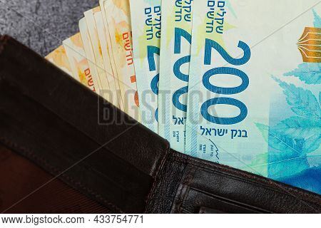 200 And 100 Israeli Shekels Banknotes Stick Out Of A Leather Wallet Close-up.
