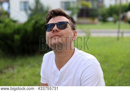 Smiling Looking Up Young Caucasian Man With Sun Glasses In A White T-shirt On Park With Blurred Sunn
