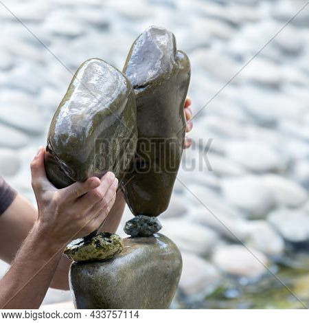 Human Hands Build A Cairn Of Stones On The Water. Balance And Meditation
