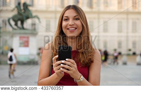 Charming Young Woman Looking At Camera Laughing Against Urban Historical City Background. Female You