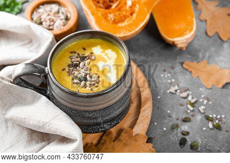 Cup Of Homemade Pumpkin Soup With Seeds, Sesame Seeds And Flax Seeds Close-up, Warm Autumn Food
