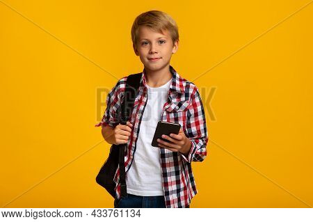 Serious Calm Cute Caucasian Young Boy Student With Backpack Typing On Smartphone