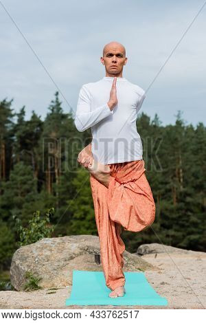 Full Length View Of Buddhist In Sweatshirt And Harem Pants Practicing Yoga In One Legged Tree Pose