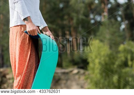 Partial View Of Buddhist In Harem Pants Holding Yoga Mat Outdoors
