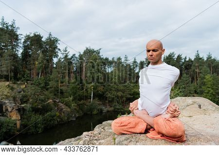 Buddhist In White Sweatshirt Practicing Extended Lotus Pose On Rock In Forest