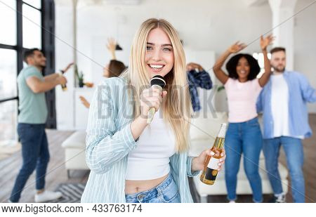 Carefree Millennial Blonde Woman With Bottle Of Beer Singing Karaoke On Party With Her Interracial F