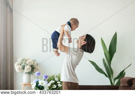 Happiness Asian Mom Playing With Her Son Newborn In Living Room Stay At Home. Asian Woman Holding An