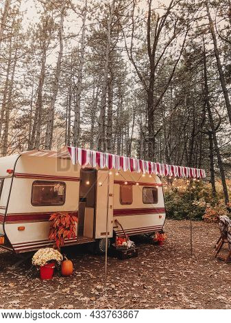 Wooden Chairs And Table With Tea Set Placed Outside Cozy Retro Caravan On Autumn Day In Peaceful Cou
