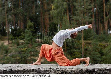 Side View Of Buddhist In Sweatshirt And Harem Pants Practicing Crescent Lunge Pose Outdoors