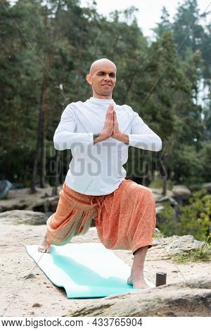 Buddhist In White Sweatshirt Practicing Yoga In Warrior Pose With Praying Hands In Forest