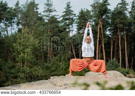 Buddhist In White Sweatshirt Practicing Goddess Pose With Raised Hands On Rocky Cliff In Forest