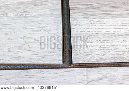 Worker Lays Laminate Flooring On A Substrate While Renovating A House. Laying Laminate Flooring - Cl