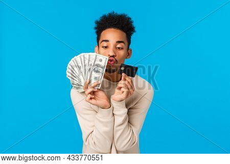 Waist-up Portrait Addicated And Pleased African-american Guy Looking At Precious Money And Credit Ca