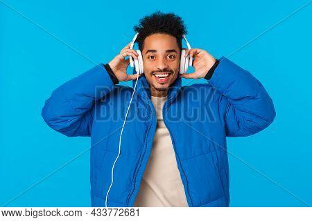 Waist-up Portrait Happy Smiling African American Guy Listening Music In Headphones, Put Earphones As