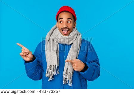 Upbeat, Amused And Cheerful African American Male In Padded Jacket, Winter Scarf And Beanie, Looking