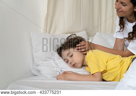 Cute Caucasian Boy Sleep In Bed With Caring Mom Sitting Close. Loving Mother Caressing Head Of Sleep