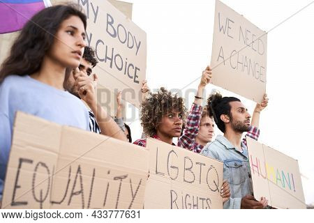 Group Of Activist People Marching On The Road In Protest At Gay Pride Day.