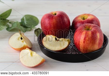 In A Round Black Dish On A White Wooden Table Are Three Juicy Beautiful Ripe Red Apples Of The Early