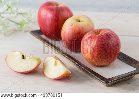 In A Rectangular Dish On A White Wooden Table Are Three Juicy Beautiful Ripe Red Apples Of The Early