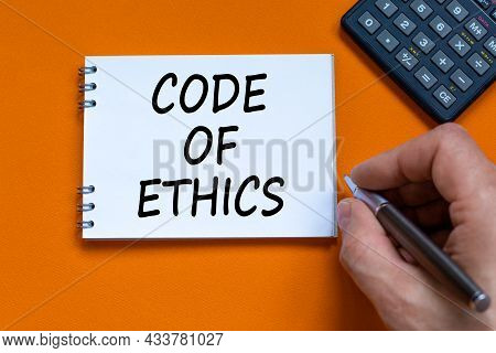 Code Of Ethics Symbol. Businessman Writing Words 'code Of Ethics' On White Note. Black Calculator. B