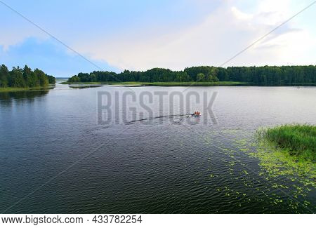 Fishermen In A Boat Fishing In The Lake. Fishing For River Fish From A Motor Boat Using A Fishing Ro
