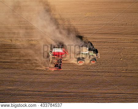 Agricultural Tractor On Cultivating Field For Sowing Seeds. Farming And Seeding Concept. Seed Sowing
