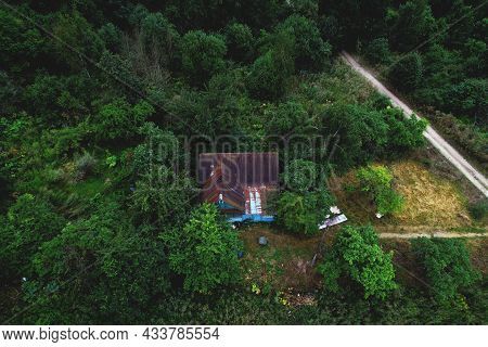 House In The Forest. Old Wooden House Stands In The Wild. Aerial View Of The Home In In Thein The Wo