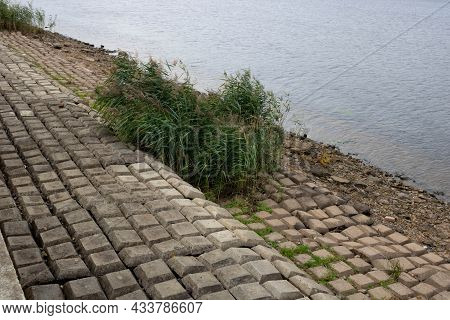 The River Banks Are Reinforced With Giant Stones As A Breakwater Against Erosion. Stone Pavement On