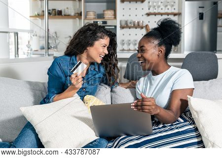 Two Young Women And Best Friends Doing Some Online Shopping At Home With A Laptop And A Credit Card