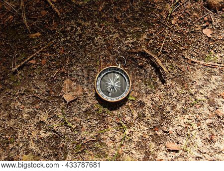 Compass On Groud In The Forest. Tourist Compass For Orientation On The Terrain. Magnetic Declination