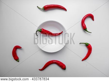 Red Hot Chili Peppers On A White Background With A White Cup In The Middle. Natural Seasoning. Fresh