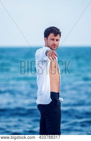 Side View Of Confident Handsome Male In Trendy Outfit Standing With Outstretched Arm Against Blue Se