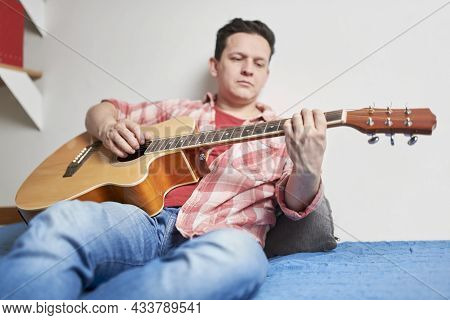 Young Man Playing Guitar In A Relaxed, Quiet Moment At Home. Concepts Of Music, Hobbies And Tranquil