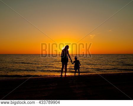 A Little Girl Holds Her Mothers Hand, Standing On The Sea Beach On A Summer Evening. In The Backgrou