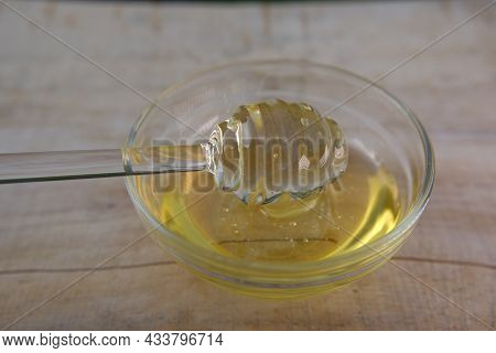 Honey. Liquid Honey In Glass Jar.glass Stick For Honey In A Glass Cup On A Wooden Table. Organic Fre