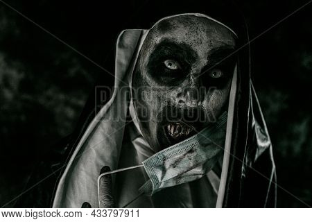 closeup of a scary evil nun, in a black and white habit, covering her mouth with bloody teeth, with a dirty disposable face mask