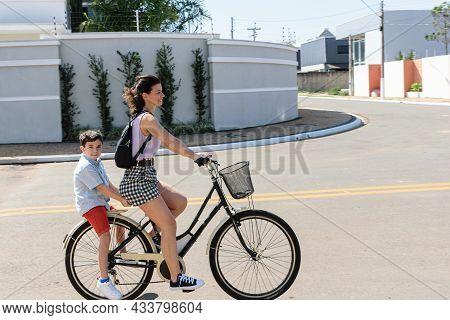 Brazilian Mother And Son Riding A Bicycle On A Sunny Morning.