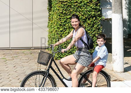 Brazilian Mother And Son Riding A Bicycle And Looking At The Camera.