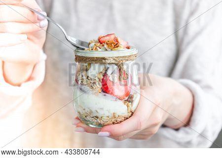 Female Hands Woman Eating Healthy Breakfast. Oatmeal Granola With Greek Yogurt And Nuts Strawberry M