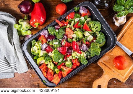 Sliced Vegetables, Broccoli, Tomatoes, Peppers And Zucchini In A Baking Sheet On The Kitchen Table W