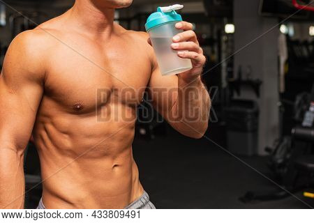 Young Caucasian Man Drinking Water After Exercise.man In The Gym Drinking From The Shaker.muscular M