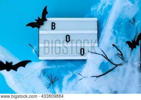 Lightbox With Word Boo And Halloween Party Decorations. Bats On Dry Tree Branch With Spider Net For