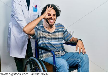 Handsome hispanic man sitting on wheelchair wearing neck collar doing ok gesture with hand smiling, eye looking through fingers with happy face.