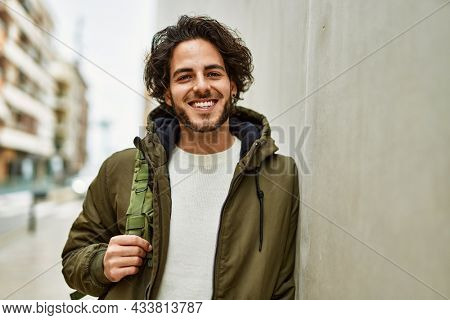 Handsome hispanic man smiling leaning on the wall