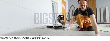 Smiling Male Construction Worker Is Laying New Floor Covering