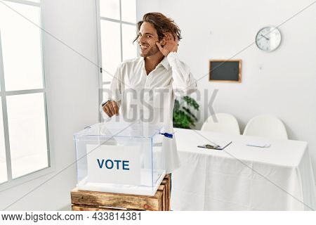 Young hispanic man voting putting envelop in ballot box smiling with hand over ear listening an hearing to rumor or gossip. deafness concept.