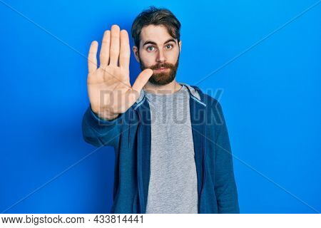 Caucasian man with beard wearing casual sweatshirt doing stop sing with palm of the hand. warning expression with negative and serious gesture on the face.