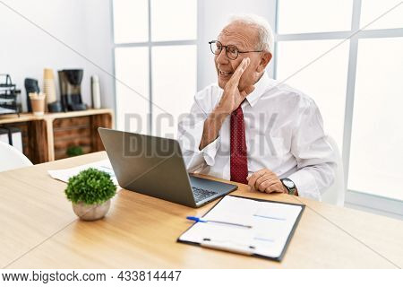Senior man working at the office using computer laptop hand on mouth telling secret rumor, whispering malicious talk conversation